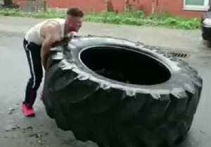 News video: Impressively Strong Man Continuously Flips Giant Tire Along Road