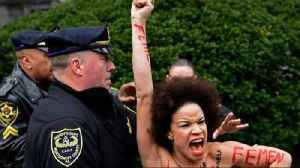 News video: Topless protester rushes at Bill Cosby as retrial begins