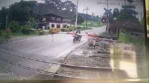 News video: Motorcyclist clotheslined by level crossing moments before train passes
