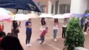 News video: Chinese teachers hold umbrellas for schoolchildren during downpour