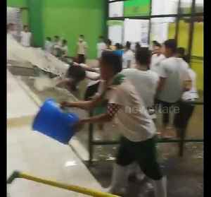 Shop workers scoop out flood water with buckets [Video]
