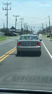 Silver car driving with blue surfboard out of driver rear passenger window [Video]