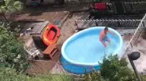 Guy records friend jumping into blue blow up pool in backyard home breaks pool water spills [Video]