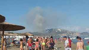 Wildfire burning in distance doesn't ruin day for beachgoers on Greek island [Video]