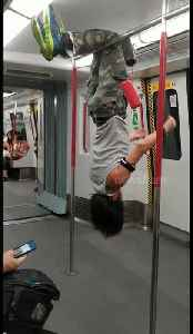 Man performs gymnastic routine, pull-ups and headstand on Hong Kong train [Video]