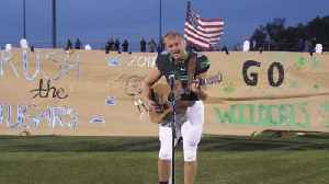 Football player stuns crowd with national anthem performance [Video]