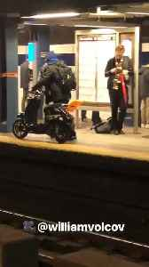Man walking through train subway station with moped scooter bike [Video]