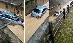 Car Washed Away After Skidding Into Storm Drain [Video]