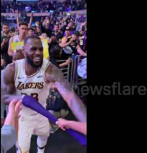 Young fan freaks out when LeBron hands his arm sleeve to him [Video]