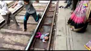 Baby escapes after slipping under moving train [Video]