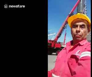 Men left hanging metres in the air after crane falls in freak accident [Video]