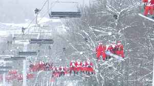 Forget rain deers! Hundreds of Santas sliding down on skies for charity [Video]