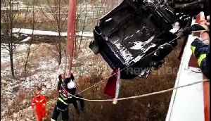 Firefighters rescue driver trapped in semi-trailer hanging off snowy motorway [Video]