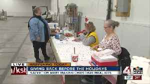Salvation Army volunteers making Christmas meal kits [Video]