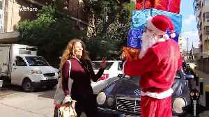 Santa 'drops' presents on people in holiday prank [Video]
