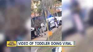 Video: Toddler walks with her hands up toward police officer [Video]