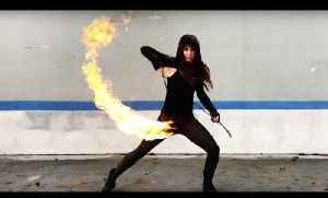 Woman Does Tricks with Flaming Rope Dart [Video]