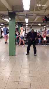 Man in black and purple suit dances crazily to a piano song in a subway station [Video]