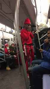 Dancer in red outfit performs on subway train,