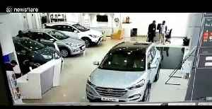 Customer smashes through car showroom window at dealership in India [Video]