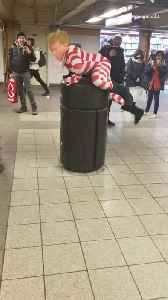 Person in donald trump mask, american flag bodysuit climbs on top trash can [Video]