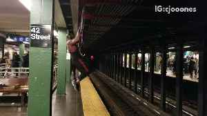Pt. 2 guy wearing headphones and tank top works out in subway station pull ups [Video]