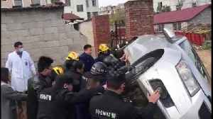 Rescue workers and passersby team up to lift car up and free trapped woman [Video]