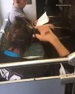 Man cutting hair with scissors on train