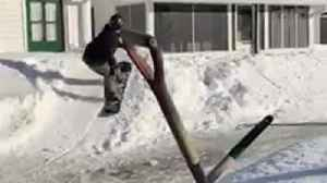 Snowboarder pulled by snow sled, jumps off ramp onto roof and falls [Video]