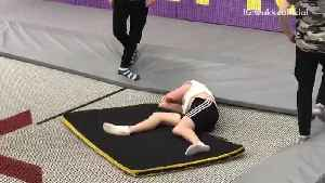 Guy does triple front flip on trampoline and gets his head stuck underneath safety mat [Video]