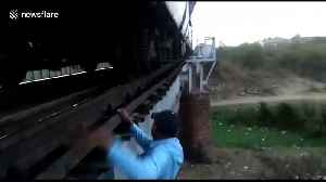 That's dedication! Brave train driver risks life to fix train after it stops on bridge in central India [Video]