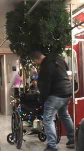 Man puts a tree in a wheelchair with flashing christmas lights on subway train [Video]