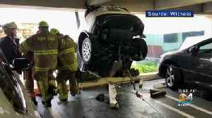 Rescue Workers Pull Woman From Dangling Car After Crash Through Parking Garage Wall [Video]