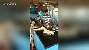 Indian paratha cook casually tosses dough over his shoulder to other chef [Video]