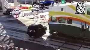 SUV drives under closing train gate and gets smashed [Video]