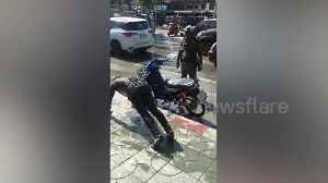 Policeman makes motor scooter rider do push-ups as punishment [Video]