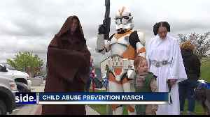 Superheroes march to prevent child abuse [Video]