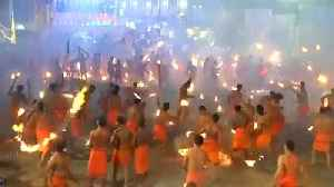 Hindu devotees throw flaming torches during Indian fire festival [Video]