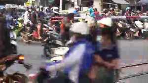 Motorcyclists risk their lives ignoring level crossing barrier as trains approach [Video]