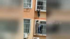 Heroic Chinese man holds up boy hanging from seventh-floor window until help arrives [Video]