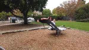Threading the needle! Acrobat leaps through hoop spinning on playground turntable [Video]
