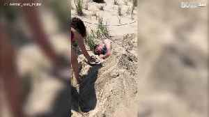 Young man is buried in sand after Memorial Day festivities [Video]