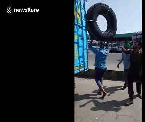 Man perfectly balances a huge tyre on his head as he climbs on the roof of a bus [Video]