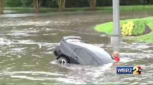Firefighters save driver after car swept away in flash floods [Video]