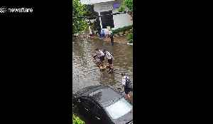Ingenious schoolboys use three wooden chairs to cross flooded road in Thailand [Video]