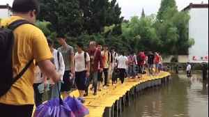 Teachers use tables to build bridge so students can walk across flooded courtyard in China [Video]