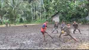 Indonesian teenagers attempt to play soccer in the thick mud of a rice field [Video]