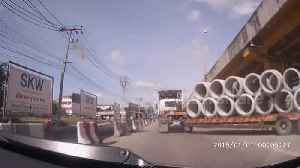 Concrete pipe falls off truck nearly crushing drivers on busy road in Thailand [Video]