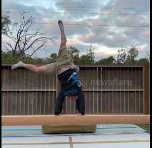 Daughter supports her dad as he attempts to cartwheel on a balance beam in Australia [Video]