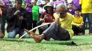 Thai pensioner born without arms has bizarre talent for firing crossbows with his FEET [Video]